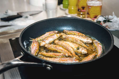 Small fish of barabul and horse mackerel are fried in oil in a frying pan on an induction cooker
