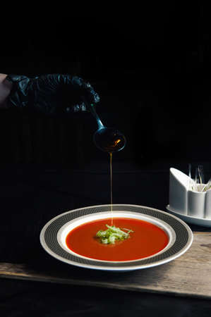 Gazpacho diet tomato soup with herbs and cucumber on a plate. womans hand fills the finished soup with olive oil.