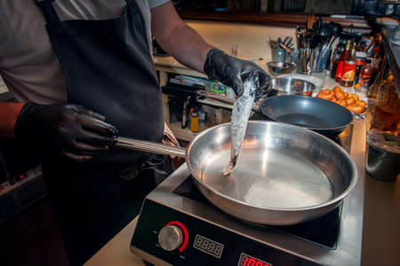 chef is frying mullet in a frying pan on an electric stove. Cooking fish dishes in the cafe Archivio Fotografico