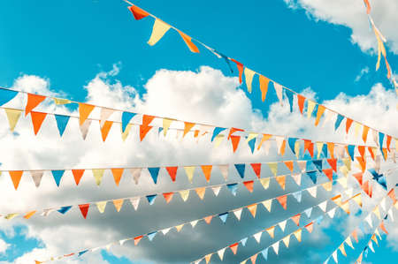 Colorful bright triangular Bunting flags on a blue sky background with white clouds. The concept of celebration and fun