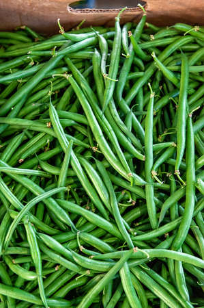Horizontal photo of a pile of freshly picked green string beans at a farmers market. Plant background Archivio Fotografico
