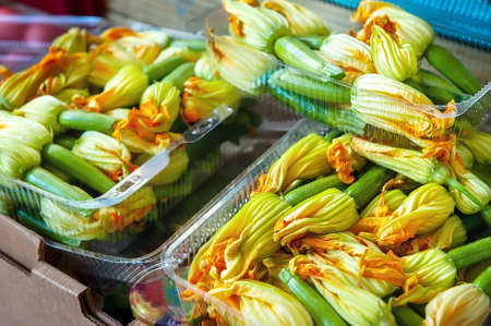 zucchini flowers and ovaries in a box for sale. Harvest delicious zucchini ovaries for cooking in batter Archivio Fotografico