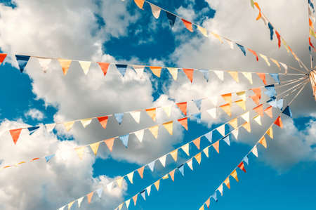 Colorful bright triangular Bunting flags on a blue sky background with white clouds. concept of celebration and fun.
