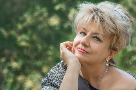 Beautiful active caucasian mature woman about 62 years old is sitting on the bench marked for social distance Archivio Fotografico