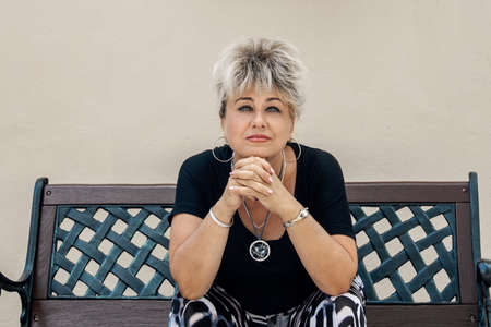 beautiful active sad Caucasian Mature woman of about 60 years old sits on a bench marked for social distance during   pandemic