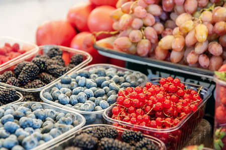 Blueberries, strawberries, raspberries and blackberries are prepared for sale at the farmers  market. Fruits on the market counter are laid out in plastic containers. Archivio Fotografico