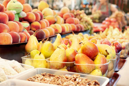 Ripe yellow pears and peaches lie on the market counter with other fruits. Farmers harvest at the market