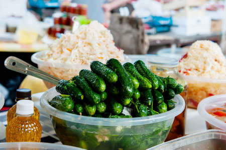 Fermented pickles lie on the counter of the farmers  market. Canned cucumbers are on sale