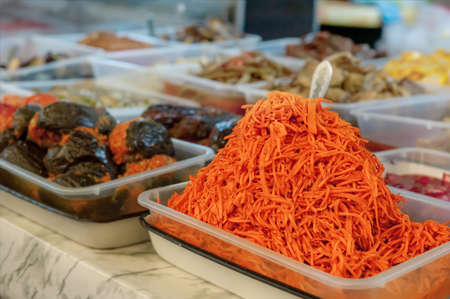 Street market stall with vegetables for sale. Fermented Korean grated carrots are sold at the farmers  market in brine