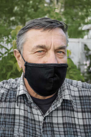 Portrait of a Caucasian old man in a crown preventive mask in isolation on the street. Large portrait of a man in   pandemic Archivio Fotografico