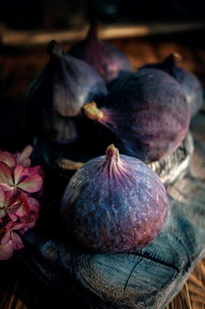 Still life fruits of ripe purple figs lying on a wooden table, close-up