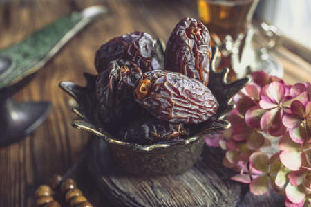 Royal gold Cup with dates for tea. Oriental holiday table, Oriental sweets for tea Archivio Fotografico