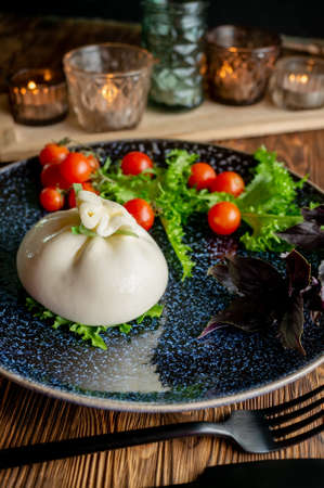 Traditional Italian dish of burrata Stratocell. Burrata on a dark plate is served for a romantic dinner with tomatoes and arugula