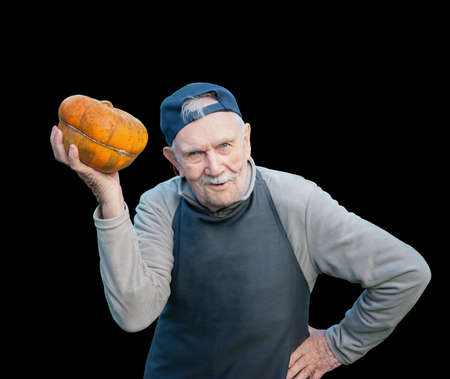 senior gardener with a pumpkin. The 87 - year-old farmer enjoys the pumpkin harvest in the garden. Cheerful active old man by nature. Isolated on black Archivio Fotografico