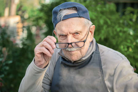 tired old man looks at his interlocutor, adjusts his glasses. The old man cant see very well without his glasses.
