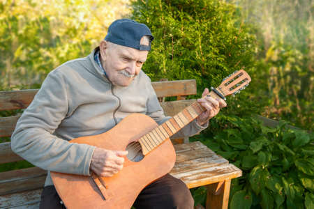 87 year-old mustachioed man plays an acoustic guitar outdoors in the garden. old man of Caucasian nationality remembers his youth and uses a musical instrument in nature
