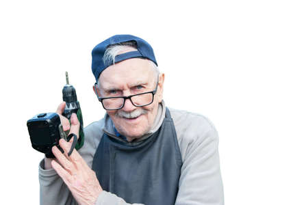 Happy old man posing with an electric screwdriver, smiling. Old farmer with a drill. Isolated on a white background