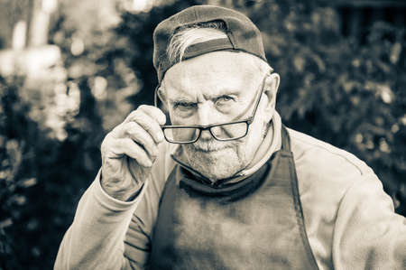 tired old man looks at his interlocutor, adjusts his glasses. The old man cant see very well without his glasses. Black and white image Archivio Fotografico