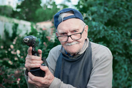 Happy old man posing with an electric drill, smiling. Old farmer with a drill. Copy space Archivio Fotografico