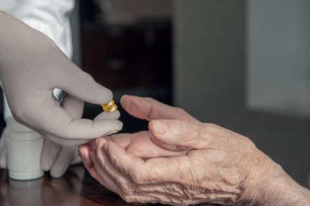 Senior man taking medication with water caring wife helping