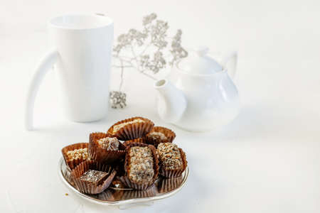 Handmade chocolate covered with cocoa and nut crumbs. Still life with sweets and tea appliances. Copy space.