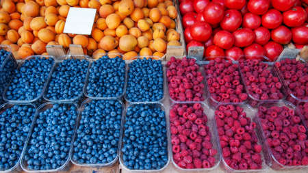 Blueberries, raspberries and blackberries are sold at the market. There are containers of berries on the counter.