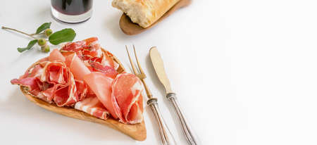 thin slices of jamon are laid out on a wooden board made of olive wood. Prosciutto served with wine, top view. copy space.