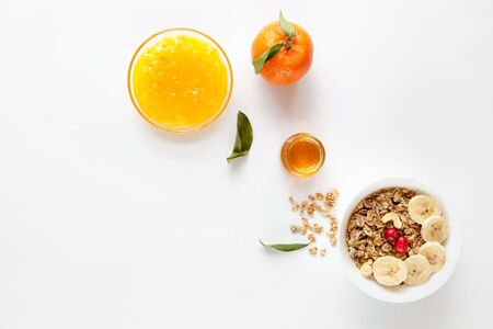 Muesli, orange, honey and jam on white background, top view