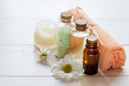 Organic cosmetics: cream, sea salt, serum, oil on white wood background, top view