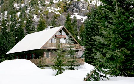 winter escape: Ski Chalet at foothill of high mountain