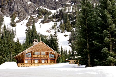 log cabin winter: Ski Chalet at foothill of high mountain