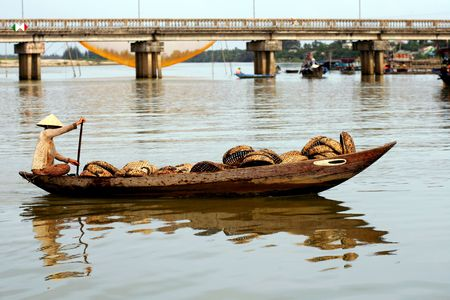 Woman in wooden boat, Hoi An, Vietnam photo