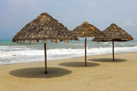 deserted: Deserted beach with three thatched umbrellas, Hoi An, Vietnam  Stock Photo