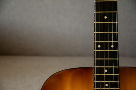 Close-up guitar fretboard with strings isolated on a blurred gray background with copy space. Music concept. Gray fabric surface. The creative process. 免版税图像