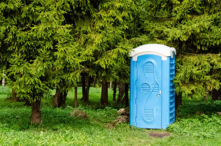 Blue plastic dry closet in the city park. Biotoilet in the recreation area. Mobile public portable toilet for walking people in the park. Pure nature concept.