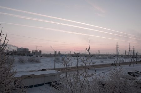 wintriness: Pink sunset on the winter industrial street with prints in the sky after the airplane View from window in the cold frosty evening. Road with cars