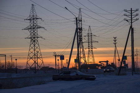 wintriness: Winter bright sunset with many electric poles and wires. North. At the polar circle Stock Photo