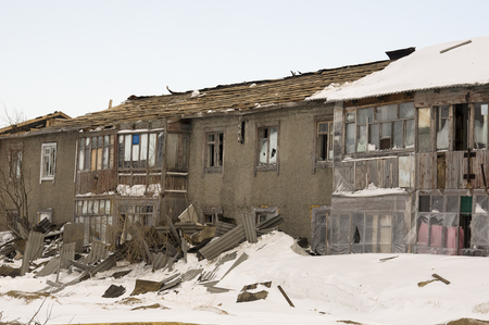 Old two-storied house in winter with snow around. Poverty and misery, North