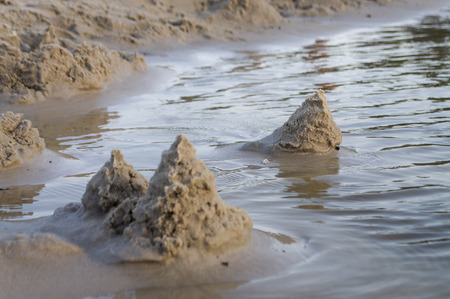 Sand castles on the bank of the river. Mild background with pastel colors and reflections in the water Stock Photo