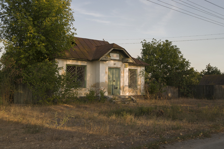 penury: Forgotten old building in little suburb. Early fall trees of green and tint of yellow colors