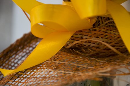 Bright yellow bow and brown wicker flower wrapping. Background