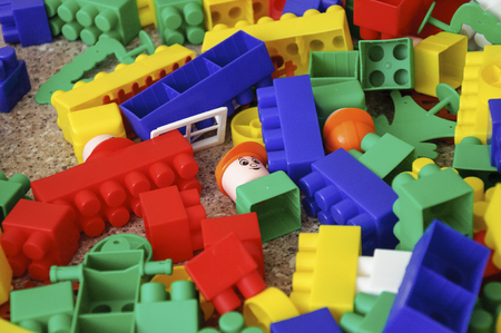 Children toys. Multi-colored plastic constructor with blocks for building houses and cars, plain, bus with figures of people