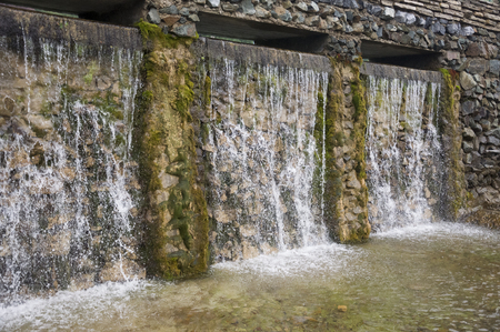 Mineral spring. Stream in the SPA. Curative water. Resort. Waterfalls. Summer. Clear and fresh water on the stone wall