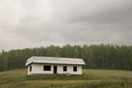 Lonely white forgotten building on the green mountain. Deep dark gray sky with a lot of clouds. Forest far away. Landscapes