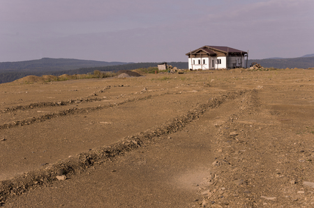 Lonely white forgotten building on the sand mountain. Deep calm blue sky with tints of purple. Ural landscapes. Brown colors. Like a desert Фото со стока