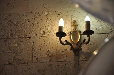 Burning candles on the stone wall in the old castle. Warm light. Decoration