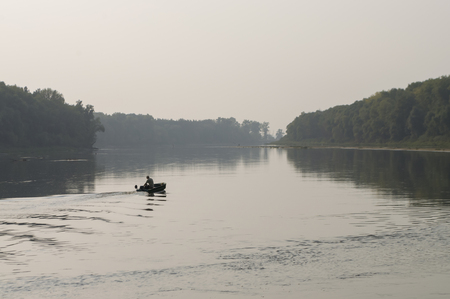Fisherman are swiming on the boat. Wide river flowing across green forest. Fall. Evening. Reflections of trees in the calm water. Sundown