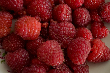 Red ripe raspberries are laying on white tablecloth