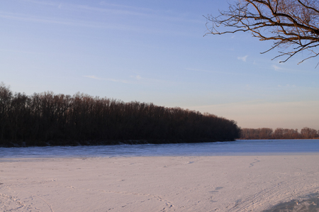 Frost river with snow and naked trees. Winter sunset in warm brown colors Фото со стока