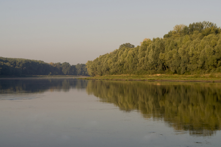 Wide river flowing across green forest. Fall. Morning reflections in the water
